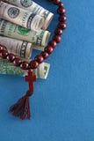 Vista superior dos dólares e dos grânulos do rosário Conceito Fotografia de Stock