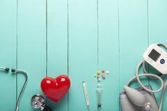 Vista superior dos estetoscópios, coração vermelho plástico, monitor e drogas portáteis automáticos da pressão sanguínea ou da fr imagens de stock royalty free