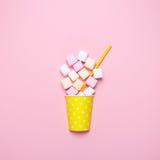 Vista superior dos marshmallows pasteis em um fundo cor-de-rosa Estilo mínimo Imagem de Stock