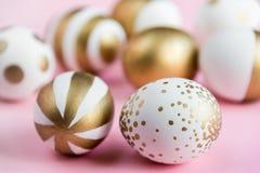 Vista superior dos ovos da páscoa coloridos com pintura dourada Vários projetos listrados e pontilhados Fundo cor-de-rosa fotos de stock royalty free