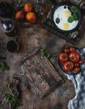Vista superior dos ovos fritos com espinafres na frigideira e nos tomates na placa Fotos de Stock