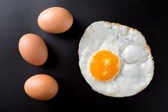 Vista superior dos ovos fritos no fundo preto, ovo Fotos de Stock Royalty Free