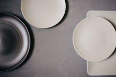 Vista superior dos pratos cerâmicos ajustados marrons e do colorido branco leitoso, no fundo cinzento foto de stock