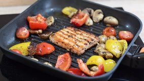Vista superior em salmões e em vegetais deliciosos na grade Close-up em grelhar pimentas quadradas dos salmões da forma, as verme video estoque