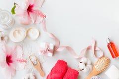 A vista superior em termas ajustou-se com sabão natural, creme, loção, toalhas e o hibiscus cor-de-rosa em um fundo branco com es Foto de Stock