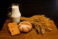 Vista superior em uma tabela de madeira com um jarro de leite, de pão de centeio e de uma polia Imagens de Stock