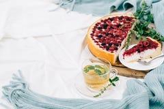 Vista superior entonada del desayuno en cama con el pastel de queso de la frambuesa, té de la menta y pagado Foto de archivo libre de regalías