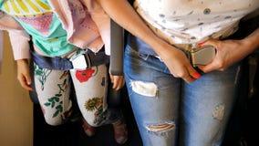 Vista superior Feche acima das mãos que prendem, curvatura da fêmea e da criança acima do cinto de segurança da cabine ao sentar- filme