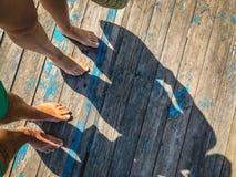 Vista superior, foto de pies desnudos y un par de sombras en un piso viejo de madera Fotos de vacaciones, playa, verano fotografía de archivo libre de regalías