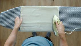 VISTA SUPERIOR: Homem adulto novo que passa uma fronha de almofada branca em uma t?bua de passar a ferro em casa video estoque