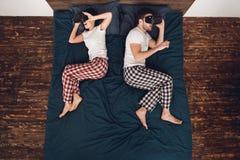 Vista superior A jovem mulher e o homem encontram-se na cama e olham-se em vidros da realidade virtual Lazer home ilustração stock