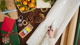 vista superior 4K de las manos femeninas que cortan el papel de embalaje para la caja con el regalo de la Navidad Foto de archivo