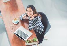 Vista superior a la sonrisa asiática casual de la muchacha y el hablar en el teléfono móvil Imagen de archivo libre de regalías