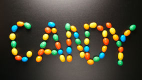 VISTA SUPERIOR: Letras dos doces por doces coloridos no fundo preto Fotos de Stock Royalty Free