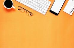 Vista superior, local de trabalho moderno com portátil e tabuleta com o telefone esperto colocado em um fundo alaranjado pastel Fotografia de Stock Royalty Free