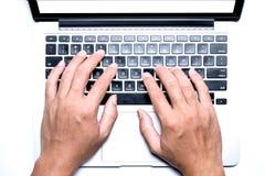 Vista superior, mão masculina do ` s trabalhando usando-se e datilografando no portátil branco com a tela branca vazia Fotos de Stock