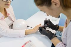 Vista superior, manicuro da mulher que faz o tratamento de mãos, pregos de pintura, usando a lâmpada ultravioleta para o verniz p imagens de stock royalty free