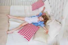 VISTA SUPERIOR: A menina alegre encontra-se em uma cama Imagem de Stock Royalty Free