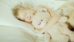 Vista superior: Menina que dorme na cama com seu brinquedo do animal de estimação filme