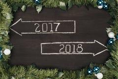 vista superior a 2017, muestras de 2018 años con las decoraciones de la Navidad alrededor en oscuridad Imágenes de archivo libres de regalías