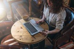 Vista superior, mulher de negócio nova na camisa branca que senta-se na mesa e que trabalha em linha no portátil ao usar o smartp imagem de stock royalty free