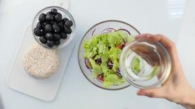 Vista superior mulher que cozinha o ponto baixo do vegetariano - a salada grega da caloria, põe vegetais em uma bacia 4K vídeos de arquivo