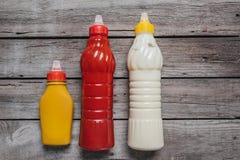 Vista superior na mostarda e na ketchup com molhos de Mayo nas garrafas que colocam na tabela de madeira foto de stock
