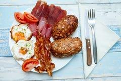 Vista superior na placa com ovos fritos, bacon, tomate e bolos, Chron Fotos de Stock Royalty Free