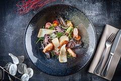 Vista superior na salada do marisco com calamar, camarão, vieiras, mexilhões, polvo do bebê, tomate de cereja e verdes A bacia de imagens de stock