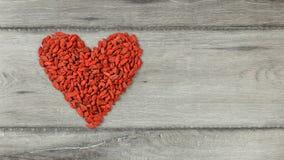 Vista superior no símbolo da forma do coração feito de bagas wolfberry do goji fotos de stock royalty free