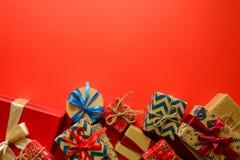 Vista superior nos presentes do Natal envolvidos no papel do presente decorado com a fita no fundo de papel vermelho fotos de stock