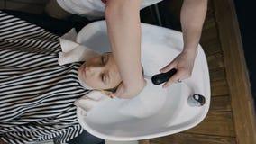 Vista superior O estilista lava o cabelo do indivíduo novo no salão de beleza ou no barbeiro Cabelo de lavagem do barbeiro do seu video estoque