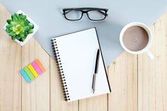 Vista superior ou configuração lisa do caderno aberto com páginas vazias e copo de café na tabela do escritório Fotografia de Stock Royalty Free