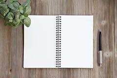 A vista superior ou a configuração lisa do caderno aberto com páginas vazias e da pena na tabela da mesa de escritório com cópia  Foto de Stock