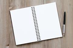 Vista superior ou configuração lisa do caderno aberto com páginas vazias e da pena na tabela da mesa de escritório com espaço da  Fotografia de Stock Royalty Free