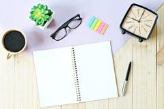 Vista superior ou configuração lisa do papel aberto do caderno com páginas vazias, acessórios e copo de café no fundo de madeira Fotografia de Stock