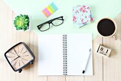 Vista superior ou configuração lisa do papel do caderno, de acessórios, do calendário do cubo e do copo de café abertos no fundo  Imagens de Stock