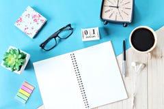 Vista superior ou configuração lisa do papel do caderno, de acessórios, do calendário do cubo e do copo de café abertos no fundo  Fotografia de Stock Royalty Free