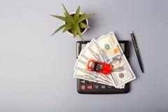 Vista superior Pouco carro vermelho sobre a calculadora e a pilha de dólares do dinheiro Despesas custadas do cálculo para custos imagem de stock royalty free