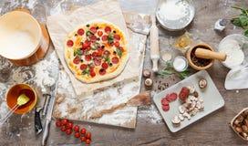 Vista superior que cozinha a pizza com ingredientes, tomates, salame e cogumelos no tabletop de madeira fotografia de stock