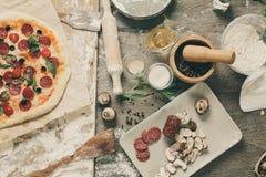 Vista superior que cozinha a pizza com ingredientes, tomates, salame e cogumelos no tabletop de madeira foto de stock royalty free