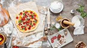 Vista superior que cozinha a pizza com ingredientes, tomates, salame e cogumelos no tabletop de madeira fotos de stock royalty free