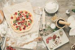 Vista superior que cozinha a pizza Ingredientes, tomates, salame e cogumelos na tabela de madeira fotos de stock