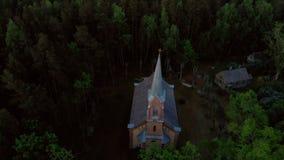 Vista superior a?rea da igreja bonita em Jurmala durante o por do sol dourado da hora - Sala Sv Ev de Janis lutheran filme