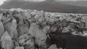 Vista superior a?rea de los cantos del glaciar blanco con la ceniza negra Iceberg esc?nico en parque nacional en Islandia almacen de video