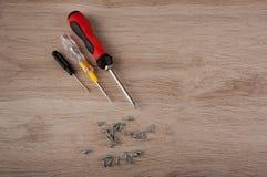 Vista superior Três chaves de fenda diferentes do tamanho e da cor e diversos parafusos colocam na tabela de madeira Fotografia de Stock