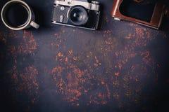 A vista superior um a xícara de café com a câmera do filme do vintage e o couro encaixota no fundo de pedra oxidado com espaço li Fotografia de Stock