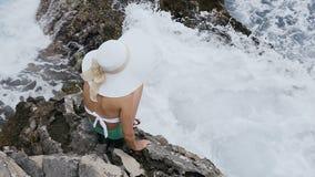 Vista superior Uma moça no chapéu que está a rocha próxima onde as ondas dividem neles perto da praia A moça está no video estoque