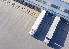 Vista superiore ad un grande magazzino di distribuzione con i portoni per i carichi ed i camion Siluetta dell'uomo Cowering di af immagini stock