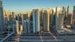 Vista superiore aerea dei grattacieli del porticciolo del Dubai durante l'alba da JLT nella notte del Dubai al timelapse di giorn stock footage